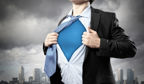 Image of young businessman showing superhero suit underneath his